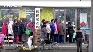 Des personnes portant des masques font la queue dans un magasin de Wuhan, dans la province de Hubei, en Chine, le 23 janvier 2020, sur cette image fixe tirée d'une vidéo.