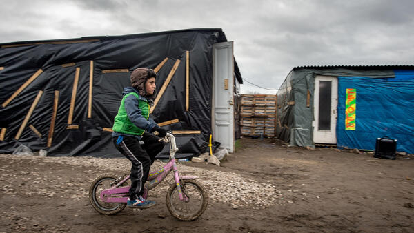 """A child rides a bike in the infamous Calais """"jungle"""", February 2016."""