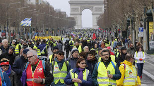 """Protesters wearing yellow vests walk down the Champs Elysees during the 17th weekend demonstration by the """"Gilets Jaunes"""" movement in Paris, France, March 9, 2019."""