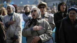 Ucranianas entoam o hino nacional durante manifestação pela unidade do país, na Praça da Independência, em Kiev.