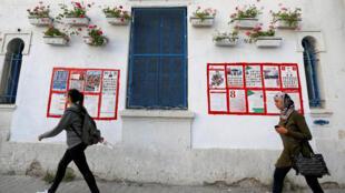 Des gens passent devant les affiches pour les élections municipales à Tunis, en Tunisie, le 27 avril 2018.