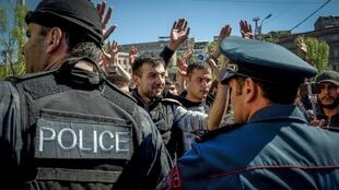 People shout and raise their hands as they face police forces during an opposition rally in central Yerevan on April 16, 2018