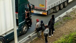 Migrants speak with a lorry driver as they walk alongside vehicles on the route leading to the Channel Tunnel in Coquelles