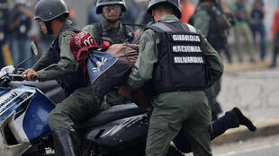 Venezuelan police tackle a demonstrator during a protest on Thursday