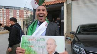 Eleitor que apoia o candidato Abdelmadjid Tebboune comemora vitória na sede de campanha depois de ter sido proclamado como novo presidente, em Argel, Argélia, 13 de dezembro de 2019.