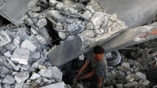Jovem palestino busca seus pertences sob os escombros de um edifício que foi destruído pelos ataques aéreos israelenses, na cidade de Gaza, em 6 de maio de 2019.