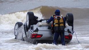 Спасатели вытаскивают из моря автомобиль, который накануне был унесен сильным потоком воды в море.