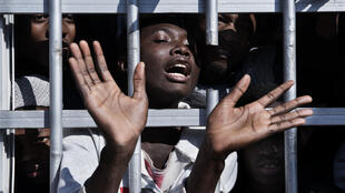 A migrant gestures from behind the bars of a cell at a detention centre in Libya, Tuesday 31 January 2017