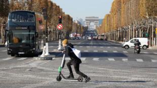 En París, un hombre atraviesa los Campos Elíseos con un monopatín eléctrico que ha arrendado gracias al sistema en libre servicio de la empresa estadounidense Lime.