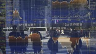 Los peatones se reflejan en el ventanal de unos paneles electrónicos que muestran las cotizaciones de la Bolsa de Tokio, el 26 de marzo de 2020 en la capital japonesa