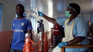 Funcionário de saúde mede a temperatura de um homem no posto de Mpondwe, na fronteira de Uganda com a República Democrática do Congo 13/06/19.