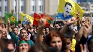 Em Bruxelas, manifestantes carregam bandeiras com a imagem de Abdullah Ocalan, líder do PKK