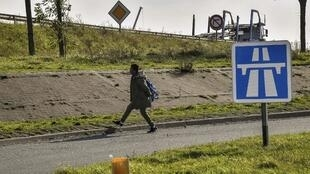 A migrant walks next to a lorry parking lot, in the French northern city of Calais.