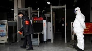 Un travailleur en tenue de protection à l'entrée d'une station de métro, à Pékin, le 27 janvier 2020.