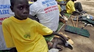 "A ""Talibe"", pupil from a Koranic school, takes a break next to a placard reading in French ""No begging for children"""