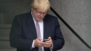 Boris Johnson uses a mobile phone as he walks through buildings inside the Houses of Parliament and Portcullis House in central London on 27 June 2016.