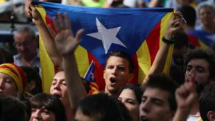 Des manifestants brandissent le drapeau catalan, devant la Haute Cour de Justice à Barcelone, le 21 septembre alors que 24 organisateurs du référendum d'autodétermination de la Catalogne étaient jugés.