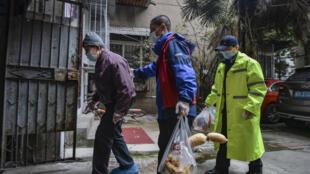 Dos voluntarios acompañan a un anciano hasta su domicilio tras recibir un pedido de alimentos, el 16 de marzo de 2020 en la ciudad china de Wuhan