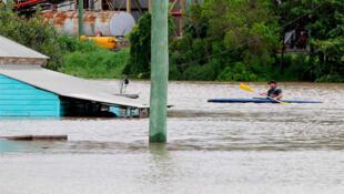 A man rows down a flooded street in Bundaberg