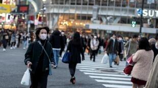 Une femme portant un masque protecteur traverse une rue de Shibuya à Tokyo, le 17 février 2020.