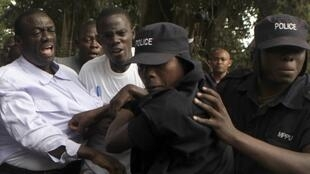 Policemen arrest opposition leader Kizza Besigye ahead of a rally to demonstrate against corruption and economic hardships