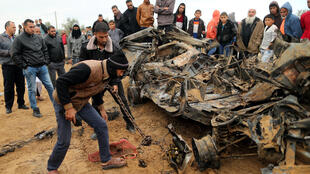 Palestinians inspect the remains of a vehicle that was destroyed in an Israeli air strike, in Khan Younis in the southern Gaza Strip November 12, 2018.
