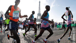 Runners make their way past the Eiffel Tower as they participate in the 42nd Paris Marathon, in France, April 8, 2018.