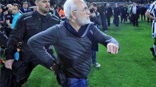 El empresario y propietario de PAOK Salonika, Ivan Savvides, ingresa al terreno de juego con una arma durante un partido contra el AEK Atenas, en Thessaloniki el 11 de marzo de 2018
