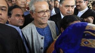 Muhammad Yunus leaves court after a hearing in Dhaka on Thursday