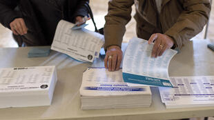 Eleitores escolhem fichas dos partidos políticos durante eleição na França.
