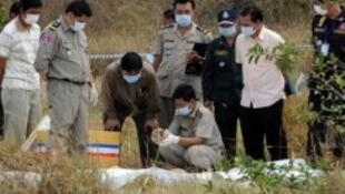 Cambodian police officials examine human remains on the propery of widower Laurent Vallier in Kampong Speu