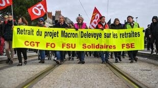 Unionists hold a banner as they take part in a demonstration against the pension reform in Nantes on January 11, 2020 on the 38th consecutive day of nationwide multi-sector strikes and protests as France's premier is due to present new proposals today.