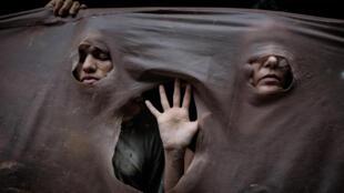 Manifestantes se cobrem de lama cenográfica em protesto contra Vale, no Rio de Janeiro
