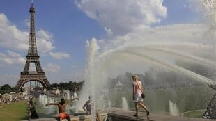 Parisians cool off in a fountain of the Trocadero Square in front of the Eiffel Tower on Friday