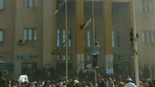 Protesters in front of a building identified as Benghazi's internal security headquarters, in a video still uploaded 20 Feb 2011