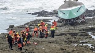 Rescuers near the capsized boat of the National Society of Sea Rescue in Les Sables-d'Olonne, where three rescuers perished during storm Miguel on 7 June, 2019.