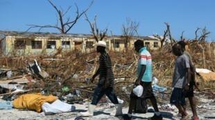 Des hommes marchent dans les décombres après le passage dévastateur de l'ouragan Dorian aux Bahamas.