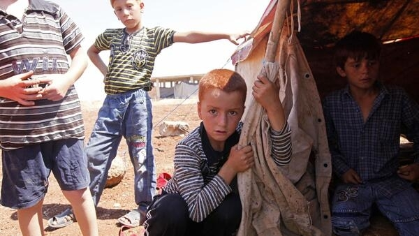 A Syrian boy sits next to his brothers by their tent at the Bab Al-Salam refugee camp in Azaz, Syria