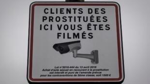 """Placa avisa: """"clientes das prostitutas, você está sendo filmado"""", e lembra a lei que pune quem contrata trabalhadores do sexo."""