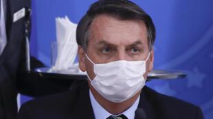 El presidente de Brasil, Jair Bolsonaro, da una rueda de prensa sobre el nuevo coronavirus, con una mascarilla para cubrirse la nariz y la boca, el 18 de marzo de 2020 en el palacio de Planalto, en Brasilia