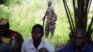 An anti-Balaka militiaman behind villagers in Bouca, Central African Republic