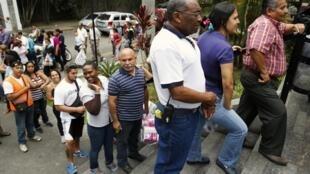 Pessoas fazem fila em frente a supermercado que recém recebeu produtos em Caracas.