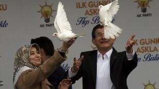 Turkish Prime Minister Ahmet Davutoglu (right) and his wife Sare release pigeons during an election rally of the AK Party in Diyarbakir on Thursday.