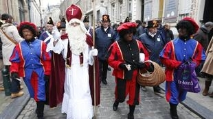 """Saint Nicholas escorted by his assistants called """"Zwarte Piet"""" (Black Pete) during a traditional parade in central Brussels. According to the folklore, Saint Nicholas arrives in the Netherlands in mid-November."""