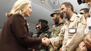 Hillary cumprimenta soldados ao desembarcar na capital líbia.
