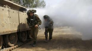 Soldados israelenses atravessam nuvem de fumaça na linha de fogo entre Israel e Síria, nas Colinas de Golan, nesta segunda-feira, 6 de maio de 2013.