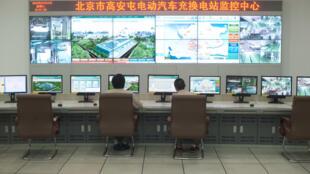 Técnicos em uma sala de controle em uma estação de carregamento de baterias de veículos State Grid, em Pequim, em 30 de maio de 2012.