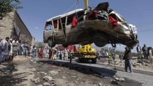 Afegãos observam a retirada de um ônibus que foi alvo de atentado terrorista que matou seis pessoas nesta terça-feira em Cabul.