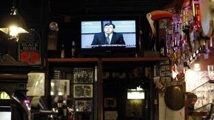 Irish Prime Minister Brian Cowen is seen delivering his four year austerity plan on a television in a bar in Dublin