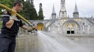 A firefighter works on the esplanade at Lourdes on Thursday